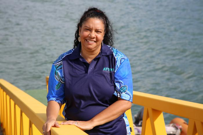 Aboriginal woman in blue shirt stands next to a yellow rail with the ocean in the background.