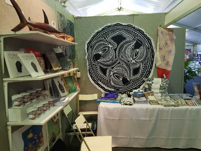 Art stall displaying craft work and books.