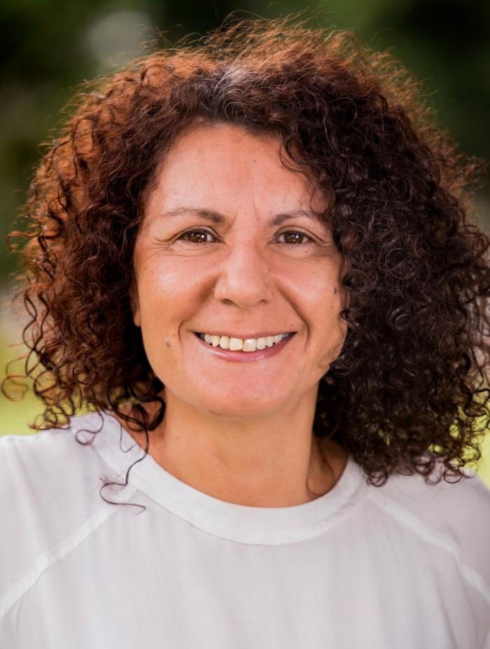 Head shot of a woman with curly hair. She is smiling.