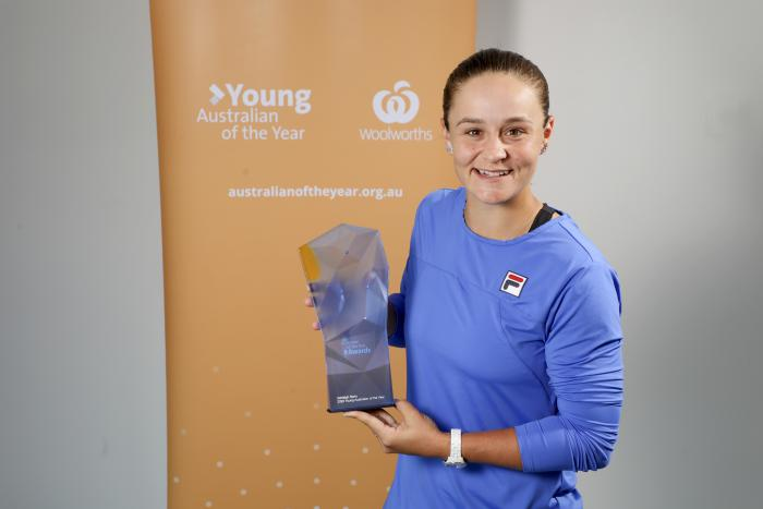 """A young woman holding a glass trophy wearing a blue shirt is standing in front of a yellow screen that reads """"Young Australian of the Year""""."""