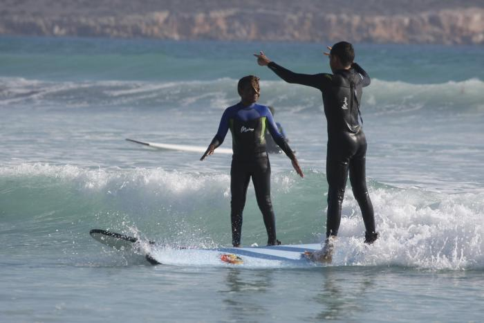 Two Aboriginal youth in wet suits surf side by side. In the background are waves on an ocean and behind that, a cliff face.