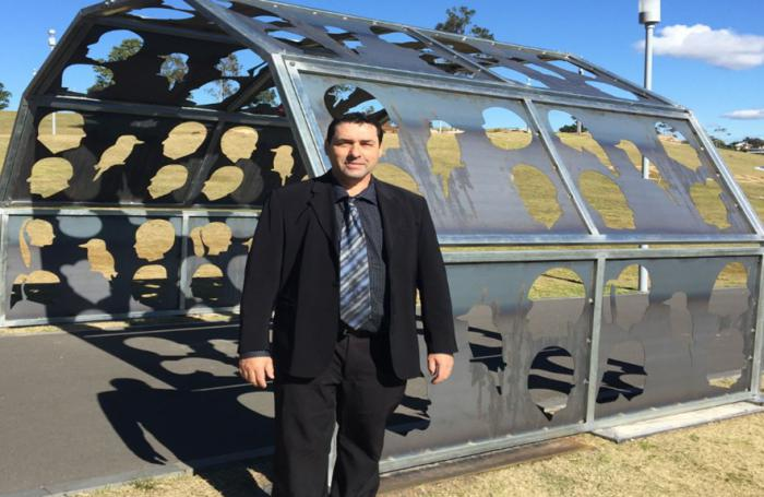 An Aboriginal man in a suit standing in front of a large outdoor metal sculpture.