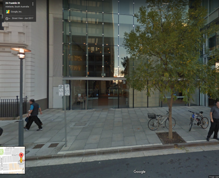 Glass front of building with grey pavers on the footpath and a tree, 2 bikes and two people in front of it.