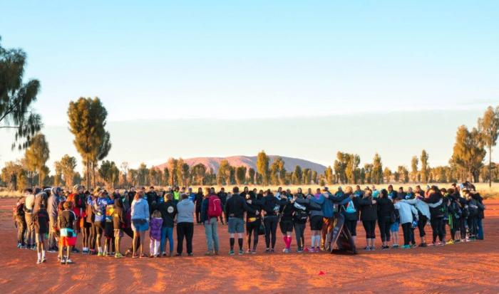 Large group of people gather in a circle on ochre red soil with trees and Uluru in the background.