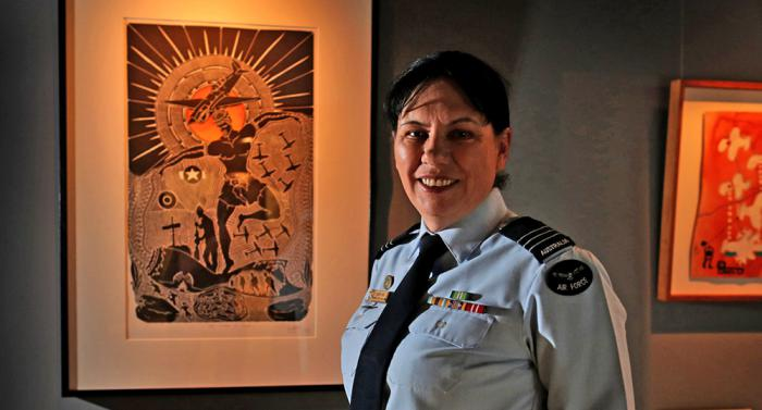 Wing Commander Cheryl Neal dressed in her air force uniform is standing in front of Indigenous artwork.