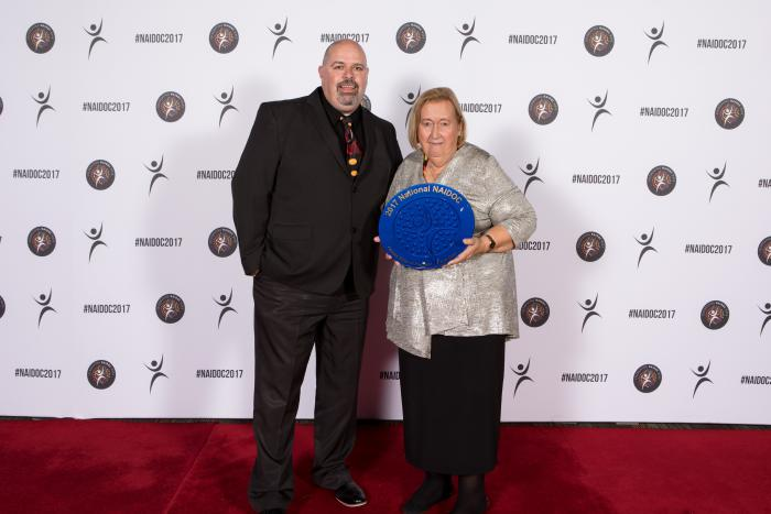 Indigenous male stands next to an older Indigenous woman on red carpet, the woman is holding large blue plate.