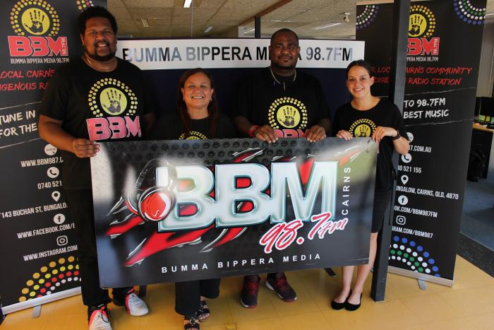 Two Indigenous men and two Indigenous women in black t-shirts stand in a room on a hard floor and behind a banner which says BBM 98.7FM. Behind them are black vertical banners with similar logos and writing.
