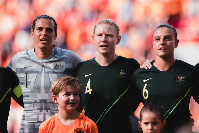 Three women (one in grey shirt and two in dark green shirts) stand arm in arm with two children in front of them. In the background is a crowd of people mainly in orange clothing.