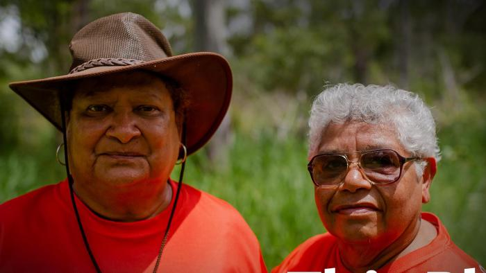 Two Aboriginal women in crimson t-shirts, one wearing a brown brimmed hat and the other with grey hair and wearing sunglasses, look to camera. In the background is green grass and trees.