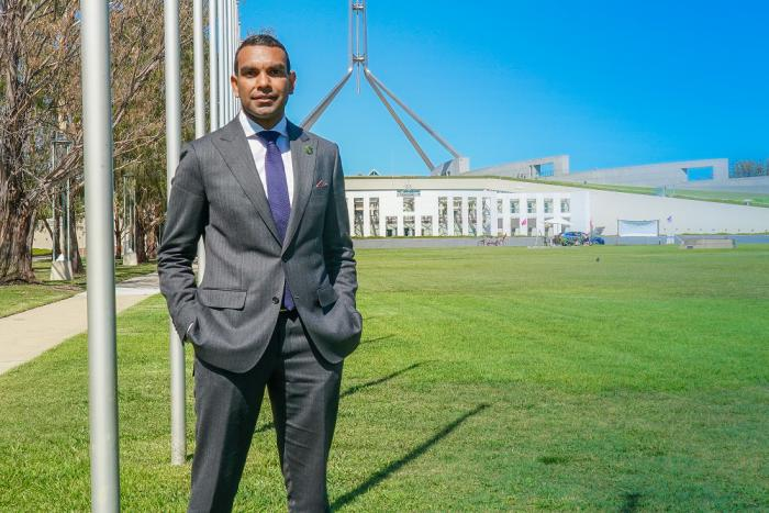 Image of a man wearing a grey suit, standing on the left, facing the camera with Parliament House behind him, a very blue sky and green grass.