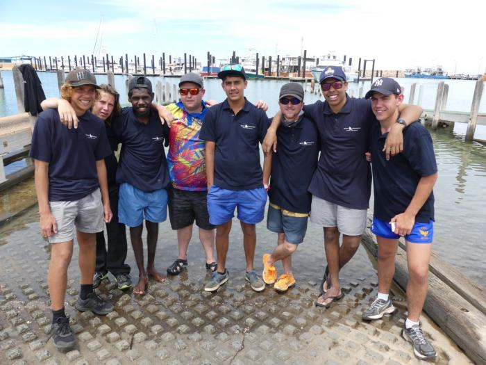 Seven young Indigenous males and one older male, dressed in shorts, shirts and hats. They are standing on a boat ramp with water lapping at their feet. In the background is a dock with boats tied up.
