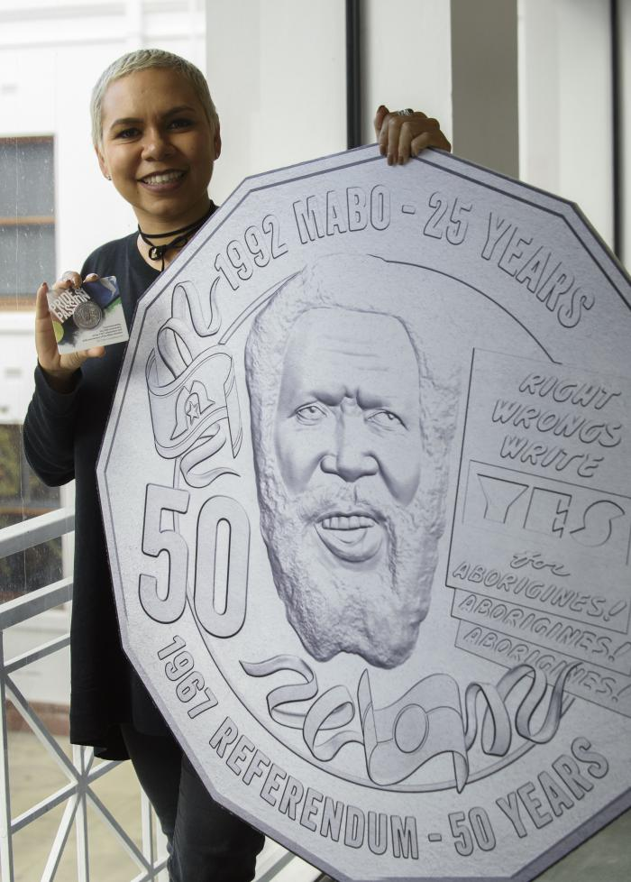 Indigenous woman dressed in black holding a 50c coin and a large replica of the coin featuring the following: face of Eddie Mabo, 1992 Mabo - 25 Years, Right Wrongs Write Yes, 50, 1967 Referendum - 50 Years, Aborigines! (three times)