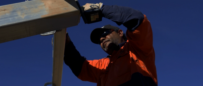 Aboriginal man in workwear, hat and sunglasses drills steel beams together. In the background is blue sky.