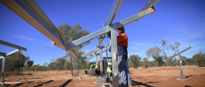 Aboriginal man dressed in workwear, hat and sunglasses works on a steel structure set on red earth with grass and trees in the background and a bright blue sky overhead.
