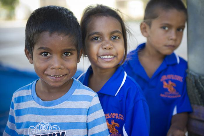 Young Indigenous male child in white and blue striped shirt in front of and to left of similar aged Indigenous girl in dark blue shirt who is in front of another Indigenous boy in same type of shirt.