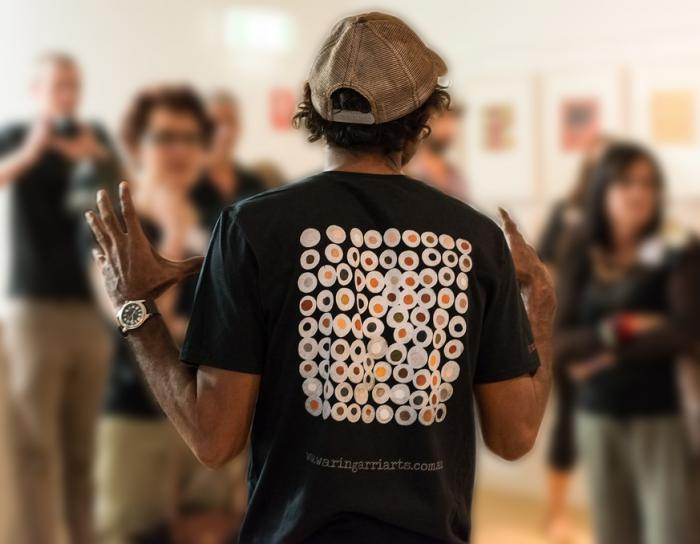 Indigenous man with back to the camera, wearing black t-shirt with Indigenous design on the back. He has his hands raised to shoulder level. In background are group of people looking at him.