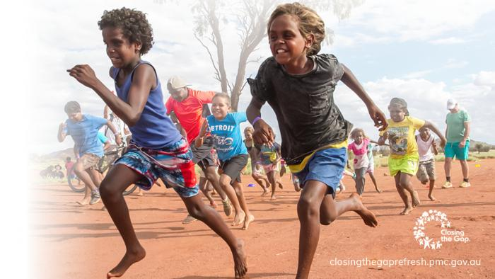 Two Indigenous boys run across red dirt with other children following behind. They are smiling. Closing the Gap logo. closingthegaprefresh.pmc.gov.au