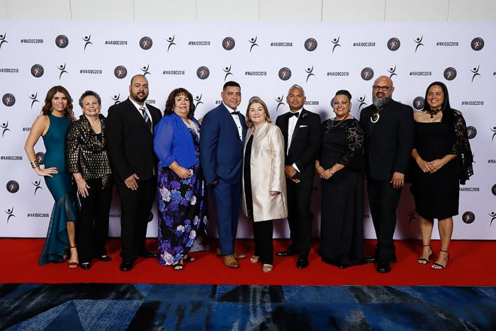 The National NAIDOC Commitee standing in front of a photo wall at the 2018 Awards