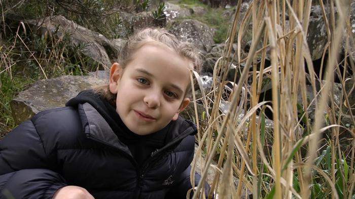 Young girl in a black jacket looks to camera. Beside her are yellow reeds and behind are rocks.