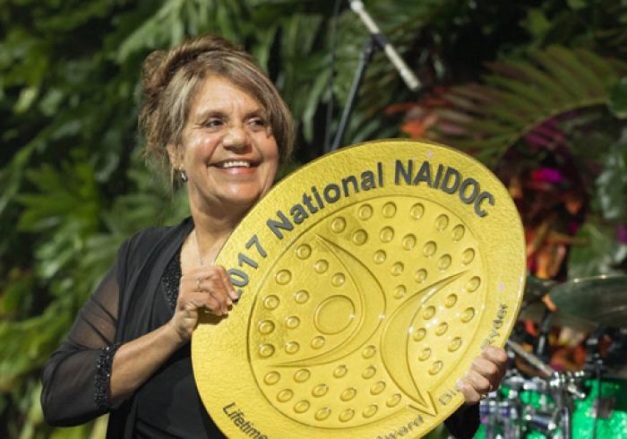 "An Aboriginal woman holding a large golden coloured plate with the words ""2017 National NAIDOC Lifetime Achievement Award""."