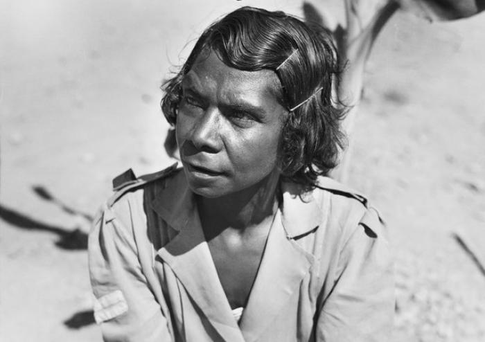 Indigenous woman with hair pinned back wearing army style clothing.
