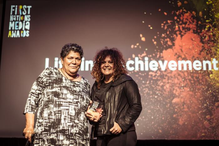 Two Indigenous women stand before a backdrop with words: First Nations Media Awards and Lifetime Achievement.