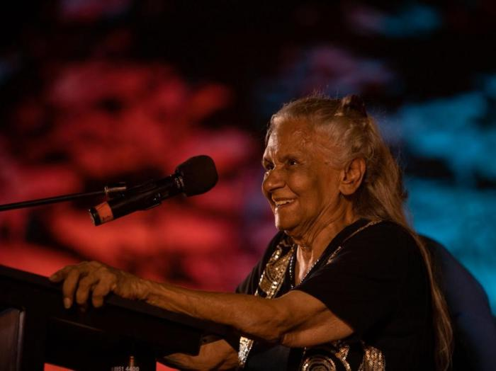 An elderly Aboriginal woman with long hair and wearing a black and gold dress stands at a pulpit with attached microphone. In the background are blue, red and black colours.