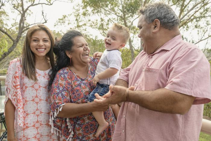 Three generations of an Indigenous family. At left is a young adult woman in pale dress. Next to her is an older woman in blue and orange dress holding a young boy in shorts and white t-shirt. At right is a man in pale pink shirt. Trees in the background.
