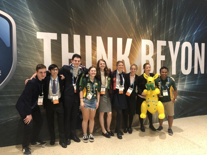 Line of young people arm in arm wearing various clothing styles stand on a hard pale surface and in front of a wall with the words in very large print: Think Beyond.