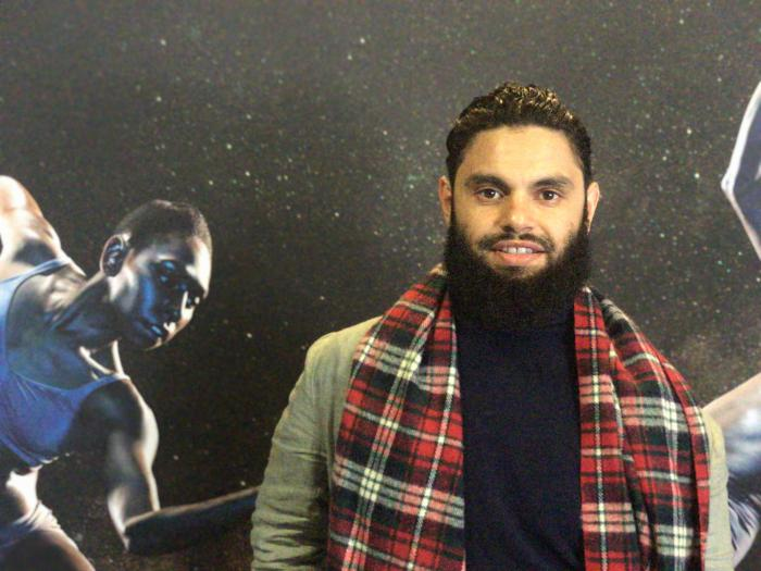 A young aboriginal man wearing a tartan scarf stands in front of a picture of a female dancer.