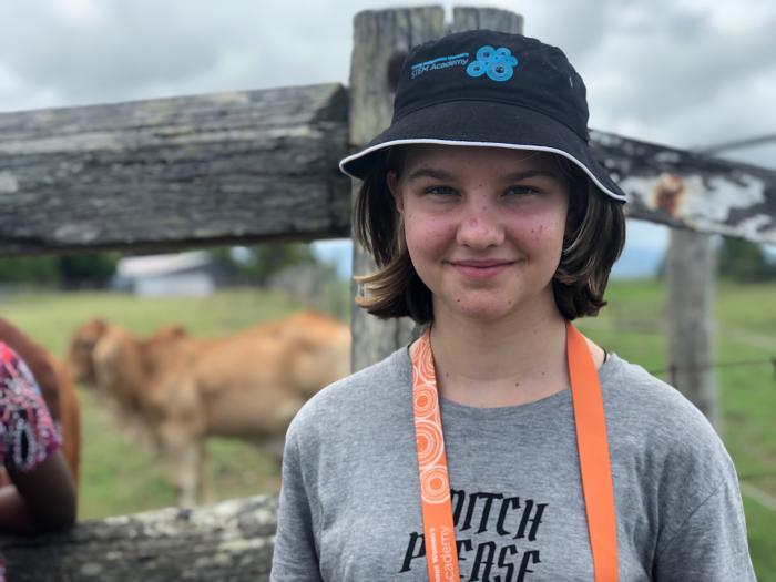 A young girl wearing a grey t-shirt and black hat, looking at the camera. She is standing in front of a paddock with cows.