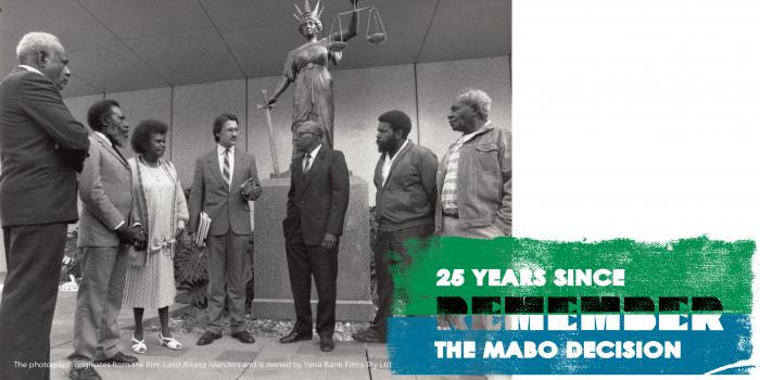 Five Indigenous men, one Indigenous woman and one non-Indigenous man stand in half circle in front of a statue of a woman holding a sword in the right hand and a set of scales in the left.  Words: 25 years sinc The Mabo Decision Remember