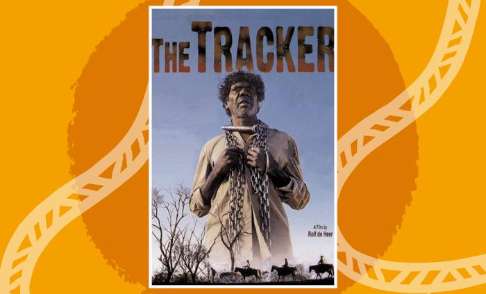 "Movie cover. ""The Tracker"" at the top, an Aboriginal man standing with shackles in his hands, blue sky behind him and at the bottom of the picture a silhouette of gum trees, three horses and four men. With the words ""A film by Rolf de Heer""."