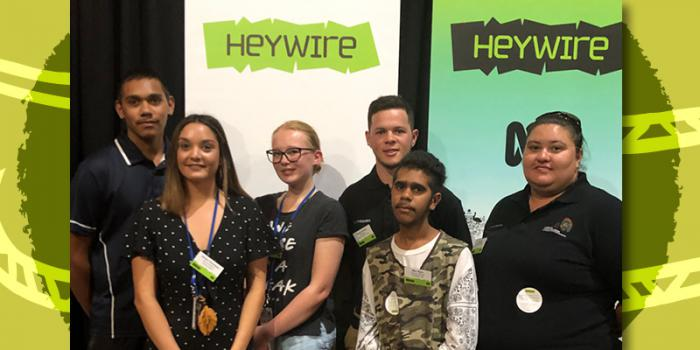 Six young people stand in front of two pull-up banners.The banners both have the word 'Heywire' written on them.
