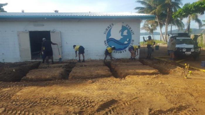 Indigenous men dressed in work wear digging trenches next to white building with blue roof with palm trees and ocean in background
