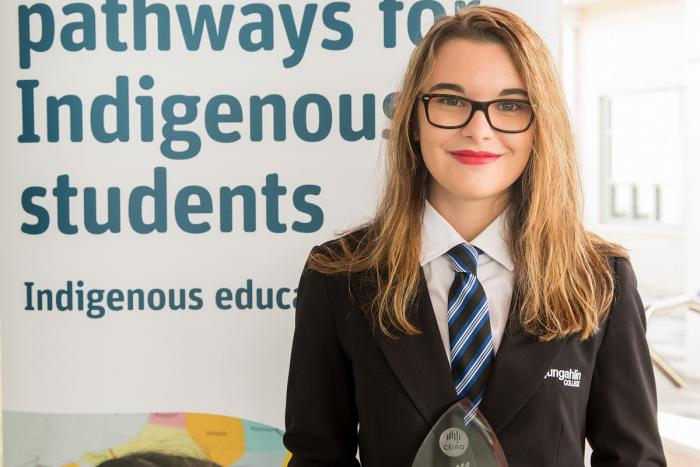 Young woman with light brown hair wearing glasses and black school jacket stands in front of a sign which says 'pathways to Indigenous students, Indigenous education'.