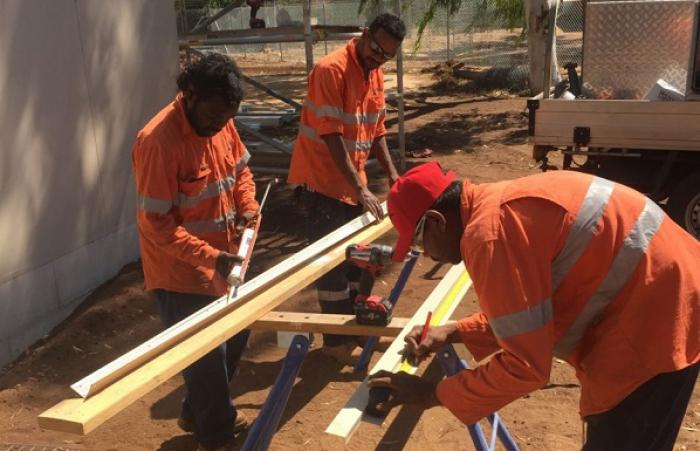 Three Aboriginal men dressed in orange work clothing and standing on red dusty soil next to a building prepare timber for use in construction.