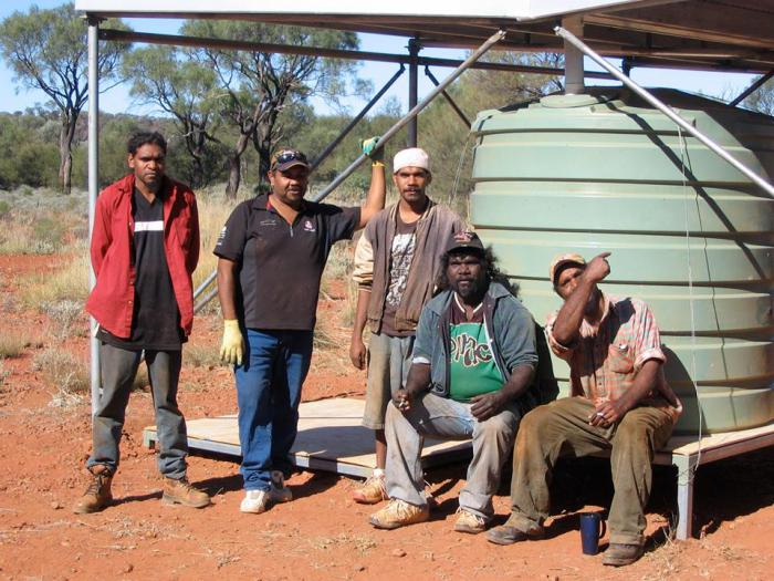 Five Indigenous men in front of a water tank
