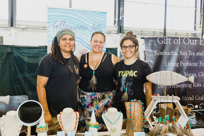 Three Aboriginal women stand behind a table covered in handmade products including necklaces and earrings. Behind them are posters with the words Gillawarra Arts on one and Gift of Our E on the other.
