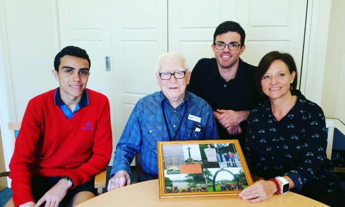 Three men and one woman seated. From left to right, student wearing red jumper, older man with glasses in checked blue shirt, man in black shirt leaning over with glasses and one woman in black patterned shirt holding photo frame.