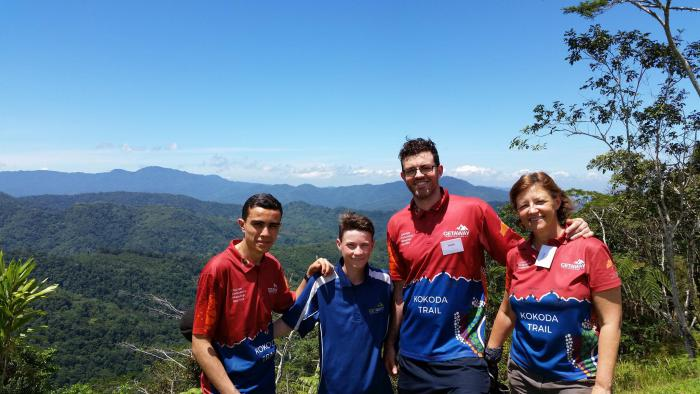 Three men and one woman wearing red and blue short sleeve shirts standing outside with mountain ranges in background.