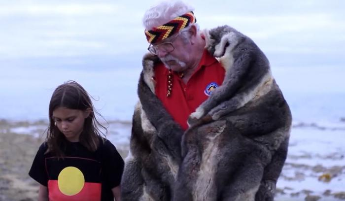 A young girl dressed in a t-shirt with Aboriginal flag design (black bar at top, red at bottom and yellow disc in middle) stands with an elderly man dressed in red shirt and fur cloak in front of a seascape.