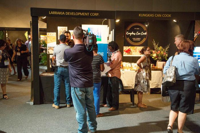 Busy trade fair floor with people in group discussions at booth. Cameraman filming.