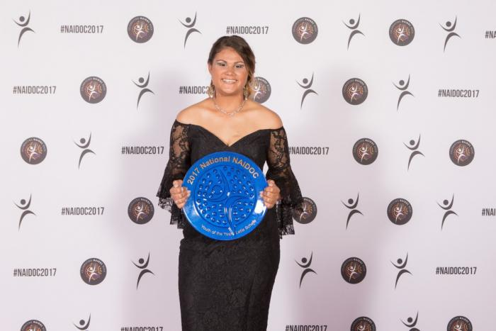 A young Aboriginal woman in evening wear holding a large blue plate.