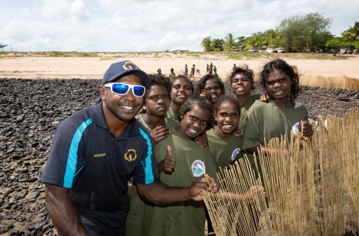 Aboriginal man in blue shirt and cap with Aboriginal youth in green shirts stand on rocks at a beach with sand and trees in the background. He supports an upright bamboo barrier.