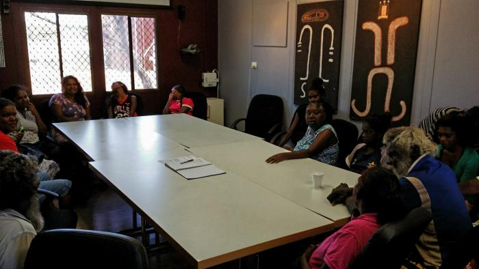 A group of Indigenous people sitting round a table in a meeting room with Indigenous art on the walls and window at one end.