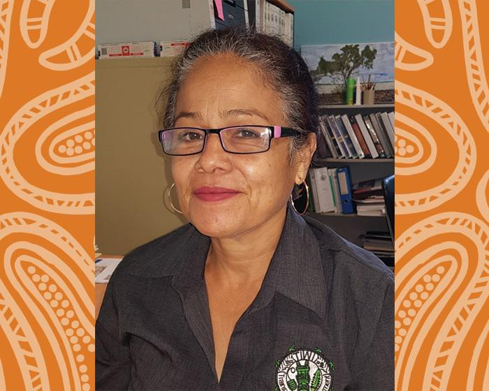 Indigenous woman with hair drawn back and wearing glasses and a dark shirt. Behind her is shelving and other office content.
