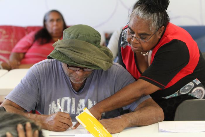 Indigenous man with green hat and grey t-shirt writes on a paper as an Indigenous woman in red and black apparel points at the paper. Another Indigenous woman sits on a couch in the background.