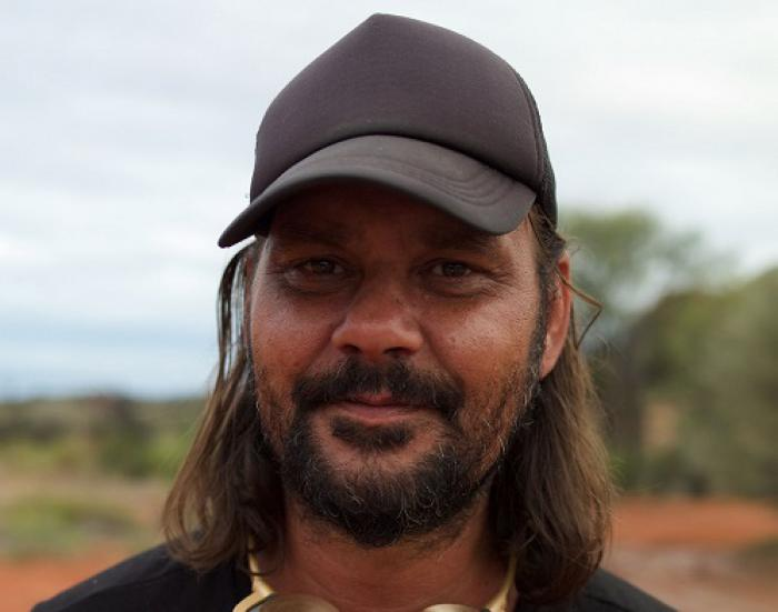 Indigenous man with shoulder length hair and beard wearing a black cap, black t-shirt stands in outback setting.