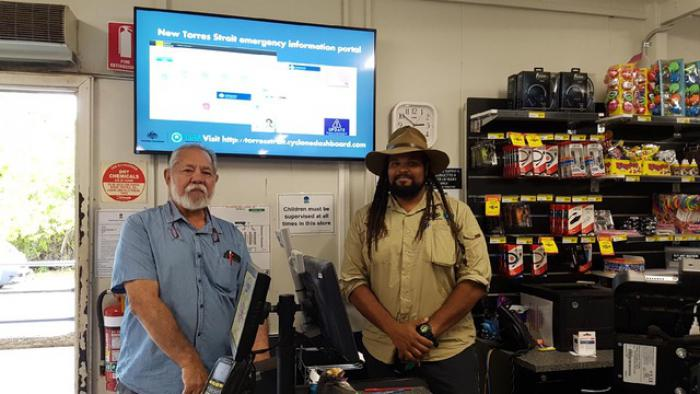 Two men stand in a shop below a large screen mounted on the wall. On the wall are also notices, a clock and a shelf of consumables. In front of them is a cash register. The man on the left wears a blue shirt and the man on the right wears a fawn shirt.